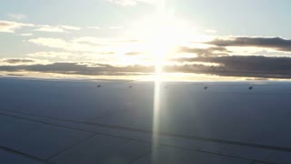 Plane wing flying over morning sunrise reflect cloud  slow motion video