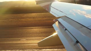 Plane wing, passenger POV taking off from runway when sunset slow motion shot