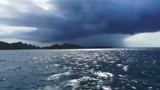 Real storm windy and raining shot in dark blue ocean. Shot with water droplet on camera while boat running