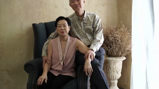 Rich Asian parents portrait with sofa in luxury home