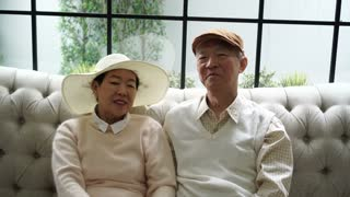 Rich Asian senior couple in sweater at luxury home sofa