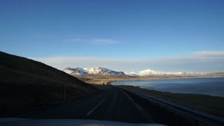 Road trip view seeing landscape of Iceland. Beautiful bay over Icelandic ocean with snow mountain background