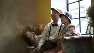 Sad Asian senior couple looking at memory photo frame