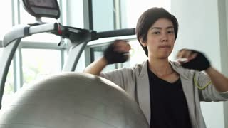 Short hair asian girl at gym with yoga ball shot. Tired exhausted but still smile