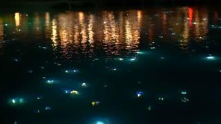 Slow motion blur beautiful light of starry night pool, illuminate fiber optic light next to restaurant