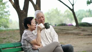 Slow motion happy Asian senior couple sitting and drinking tea, coffee in morning park. Having conversation and showing love