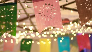 Slow motion shot of Colorful festival flags at night with garland light bokeh decoration