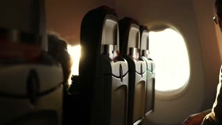 Sun light shine in airplane window. Beautiful scene lighting and silhouette of passenger seat rows