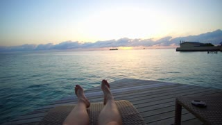 Sunrise over Maldives ocean. Feet laying relax atmosphere at private villa terrace 4k
