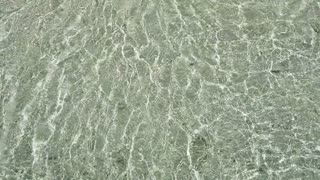 Top View of crystal clear ocean waves. Splashing over white soft sand beach in slow motion