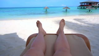 Tourist feet with white sand at paradise beach ocean slow motion video