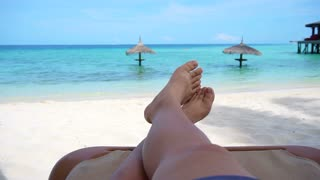 Tourist legs bare feet sitting on golden sand beach bench point out to tropical ocean paradise