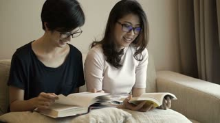 Two adult Asian women reading books at home. Spend quality time learning something new