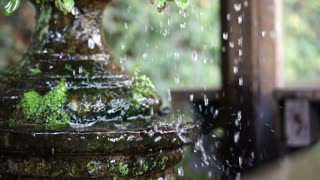 Water Drops and droplets from clay pot in tropical green garden slow motion 120 fps