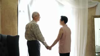Wealthy Asian senior couple parent holding hand in front of light curtain