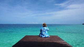 Woman back relaxing looking at turquoise paradise island ocean on wood deck