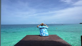 Woman relax at bright blue summer ocean. Enjoying sea breeze on vacation 4k