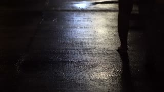 Woman walking alone in dark wet street at night abstract crime