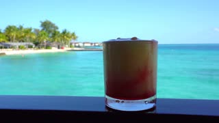 Yellow bright summer tropical cocktail at beach bar with beautiful tropical ocean