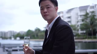 Young Asian business man holding champaign in suit talking