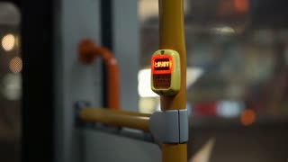 View inside the night city bus. Abstract public transportation in Asia. Stop button in car