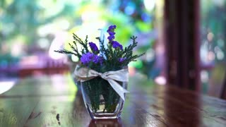 Violet flower and glass vase decorate on wood table in the garden