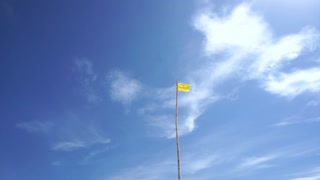 Yellow safety beach warning flag of ocean hazards and surf conditions with beautiful cloud blue sky