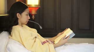 Young people at home, leisure and relax, portrait of beautiful Asian girl reading book on bed