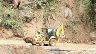 Clearing a landslide on a dangerous mountain road. In the Andes, Ecuador