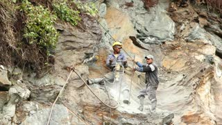 Drilling holes in a cliff face for blasting in the Ecuadorian Andes