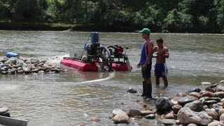 Suction dredge mining placer gold deposits on an Amazonian riverbank