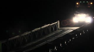 Truck crossing a Bailey Bridge at night