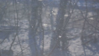 A blue background of falling snow in the rays of the sun