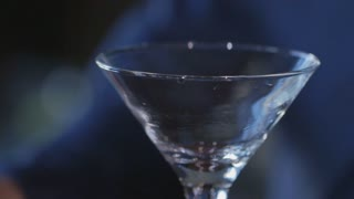 A Cosmopolitan being poured into a cocktail glass