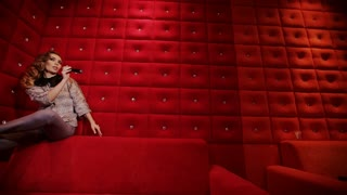 A elegant girl is sat on the edge of a vintage red sofa and is singing karaoke