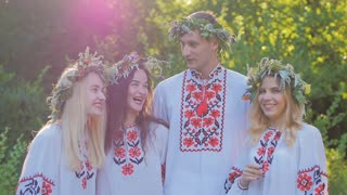a group of girls and boys in the Slavic national dress in the woods smiling and talking. The celebration of the summer equinox.