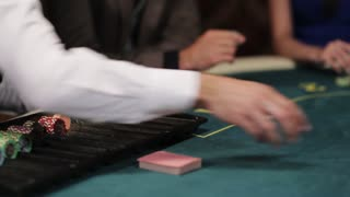 A group of people in an underground casino bet. The dealer deals the cards.