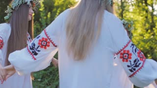 a group of young people in national Slavic costumes dance in a circle around the fire. National Slavic rites and dances in Slow motion. Midsummer.