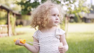 A little girl blowing soap bubbles, closeup portrait beautiful curly baby.