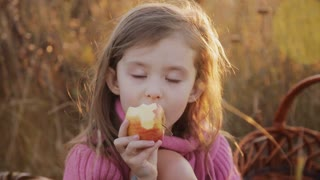 a little girl eating an apple in the sunset light