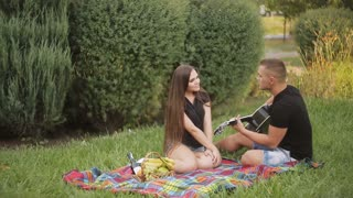 A romantic date on nature. Young beautiful couple smiling, resting in park. Man playing guitar.
