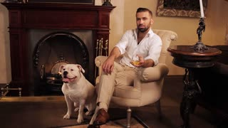 A wealthy man is sitting in a chair in the room with the fireplace and drinking whiskey. Faithful dog lies at the feet of the master.