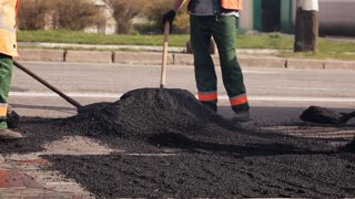 A worker is leveling deformations with cold asphalt on a rural road.