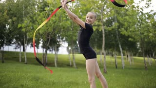 A young gymnast with ribbon performs exercises in the Park.