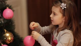 Adorable little girl decorating a Christmas tree with colorful glass baubles at home