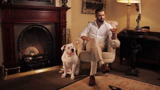 An aristocrat with a dog by the fireplace drinking whiskey.