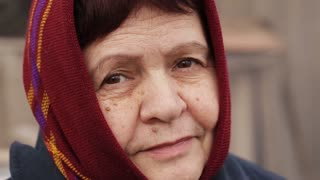 an elderly woman in a scarf smiles sadly outdoors