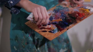 artist squeezes out a tube of paint on the palette. close-up