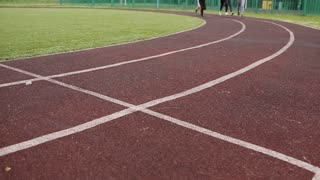 athletes, mans and womans running on running track