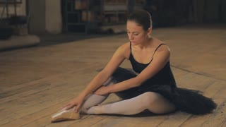Ballerina tying pointe ballet shoes on stage.